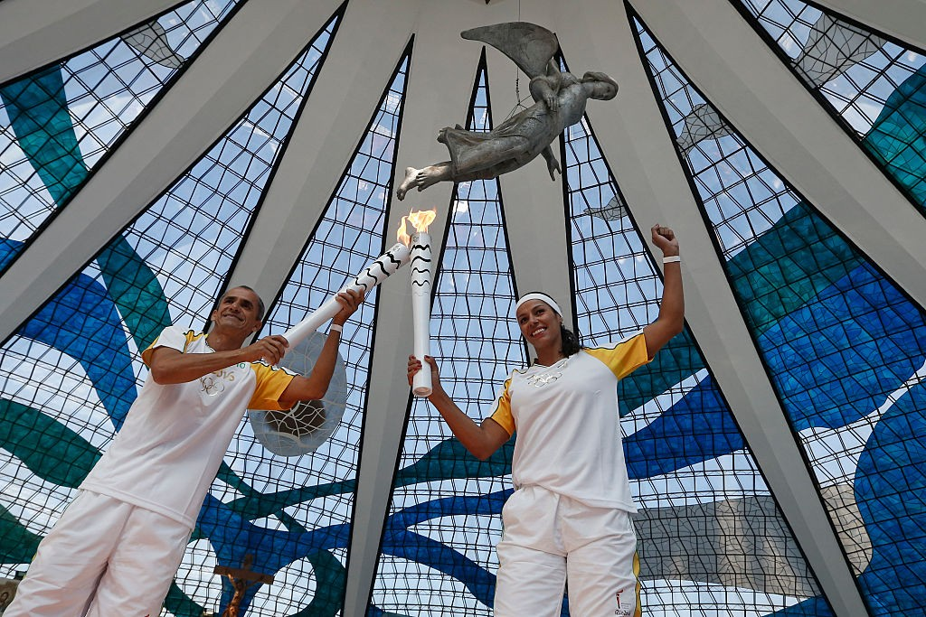 BRASILIA, DF - MAY 03: Former Marathon runner Vanderlei Cordeiro passes the Olympic Torch to Paula Pequeno in Cathedral of Brasilia during the Olympic Flame torch relay on May 3, 2016 in Brasilia, Brazil. The Olympic torch will pass through 329 cities from all states from the north to the south of Brazil, until arriving in Rio de Janeiro on August 5, to lit the cauldron. (Photo by Handout/Getty Images)